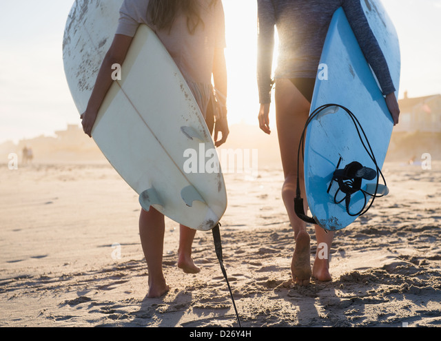 USA, New York State, Rockaway Beach, Two female surfers walking on beach - Stock Image