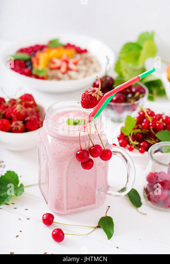 Yoghurt-strawberry smoothies in a jar on a white background - Stock Image