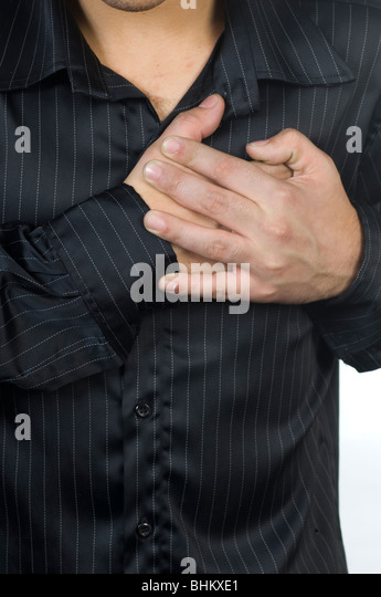 Young man hands over chest having a heartattack - Stock Image