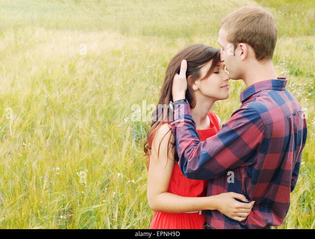 stunning sensual outdoor portrait of young stylish fashion attractive couple in love kissing in summer field - Stock Image