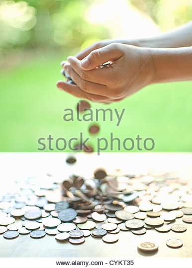 Hands pouring change on table - Stock Image