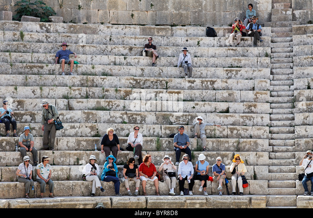 Tour group sitting in the South Theatre of Gerasa, Jerash, Jordan - Stock Image