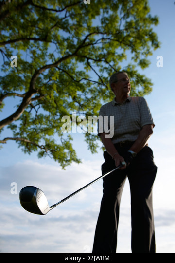Golfer standing on tee about to drive ball - Stock Image