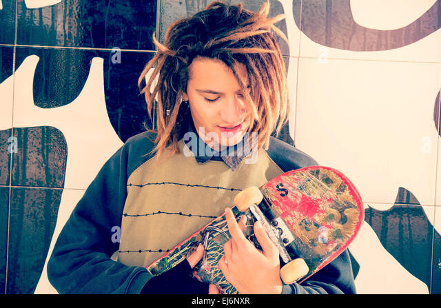 portrait of young guy  with skate and rasta hair in a lifestyle concept warm filter applied - Stock-Bilder