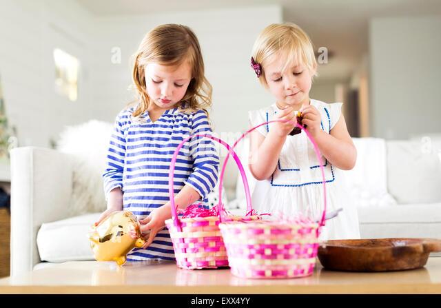 Girls (2-3, 4-5) opening candies - Stock Image