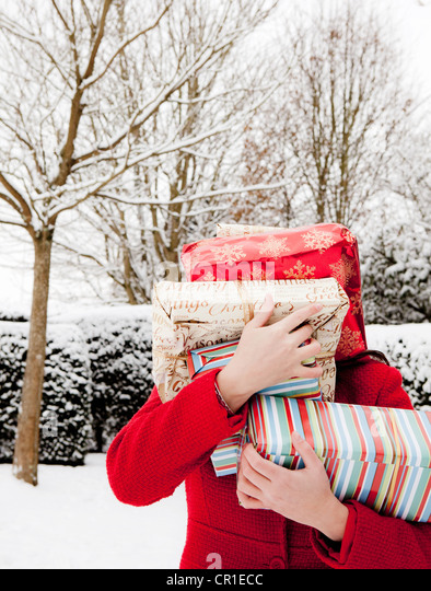 Woman carrying wrapped gifts in snow - Stock Image