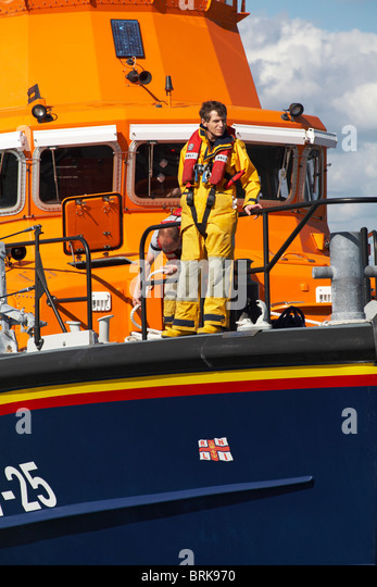 RNLI crew returning after a rescue in Yarmouth, Isle of Wight - Stock Image
