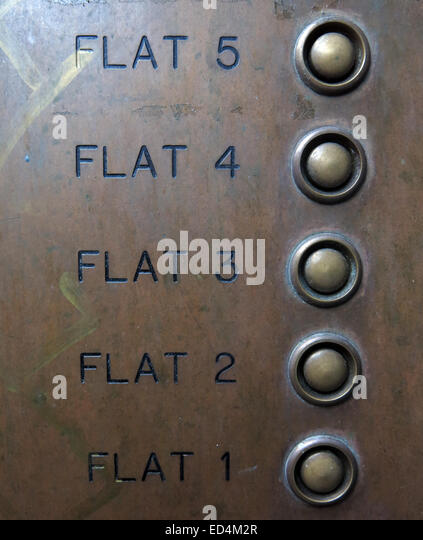 A brass plate with buzzers for flats 1 to 5 with buttons linked to bells - Stock Image