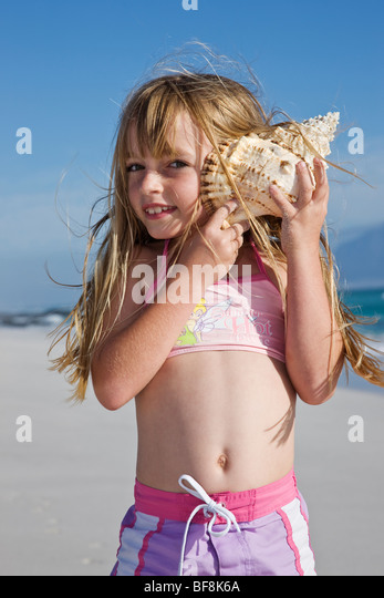 Cute little girl holding shell to ear on beach. Cape Town South Africa - Stock Image