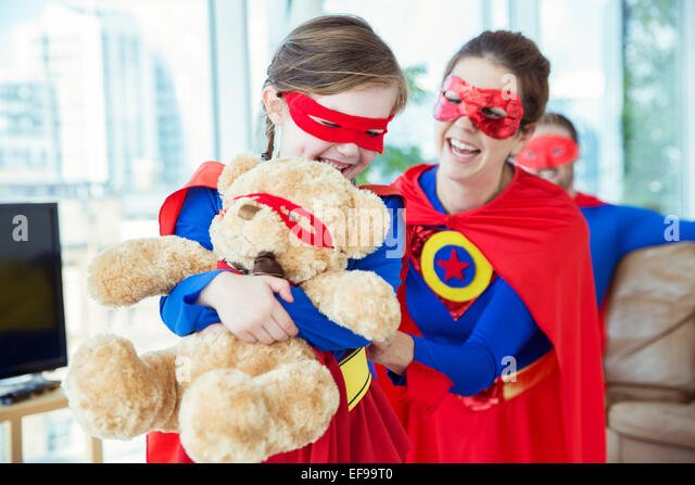 Superhero mother and daughter playing with teddy bear - Stock Image