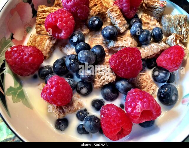 A bowl of whole grain cereal squares with raspberries and blueberries. - Stock Image