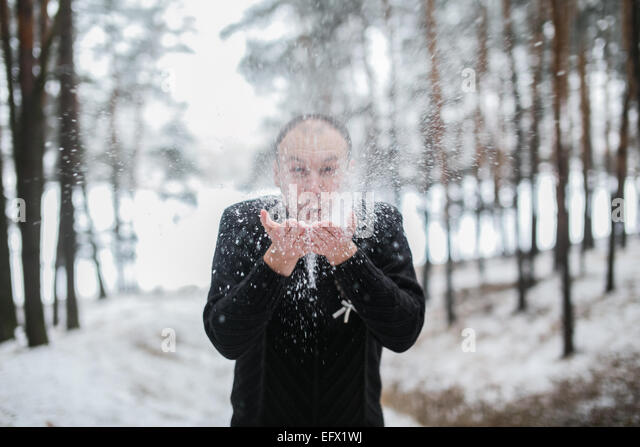 Groom blowing snow off his hands in a snow-covered winter forest - Stock-Bilder