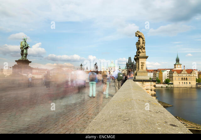 People bustling across the Charles Bridge in Prague rendered into a blur by a long exposure - Stock Image