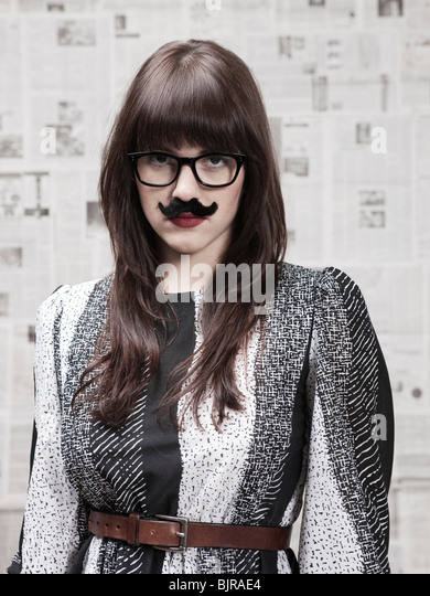 Studio portrait of young woman wearing fake moustache - Stock Image