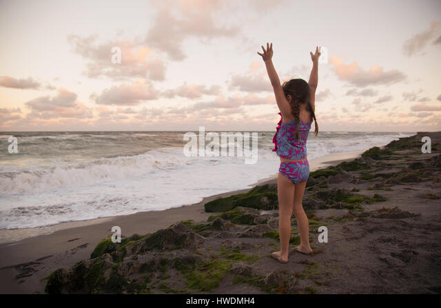 Girl at beach arms raised looking away at view, Blowing Rocks Preserve, Jupiter, Florida, USA - Stock-Bilder