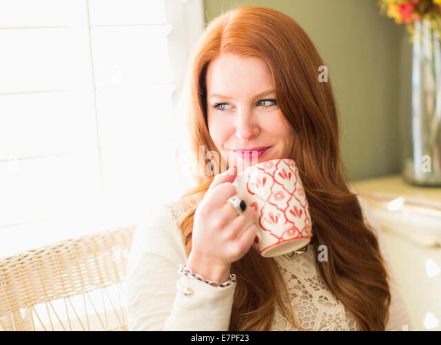 Mid adult woman drinking from coffee mug - Stock-Bilder