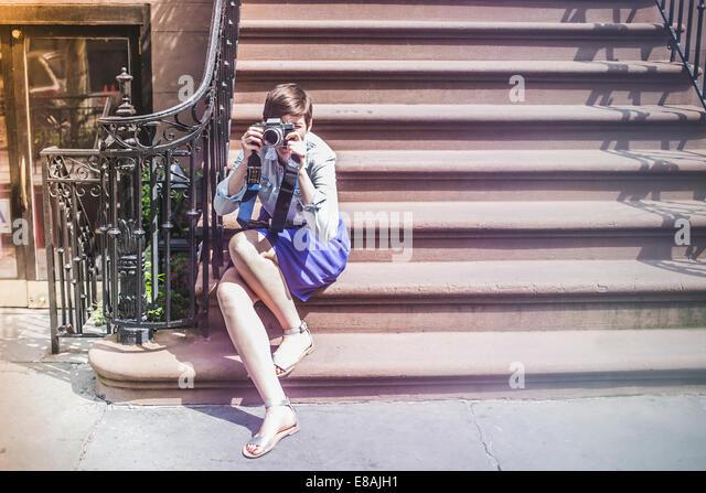 Photographer sitting on steps, New York, US - Stock Image