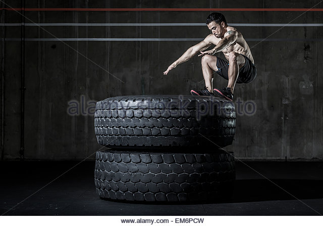 A shirtless male weightlifter and CrossFit athlete performing a box jump on two tires  in a CrossFit gym. - Stock Image