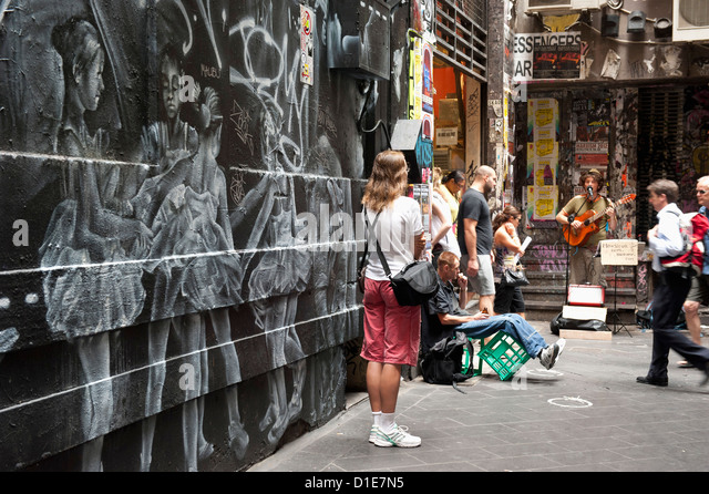 Graffiti and people watching street musician, Central Place, Melbourne, Victoria, Australia, Pacific - Stock Image