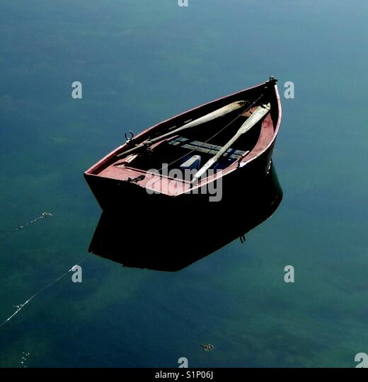 Rowing boat on the mirror-like surface of a lake - Stock Image