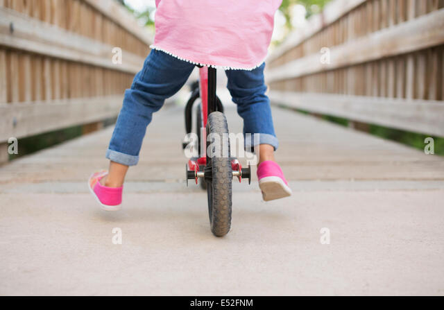 A child riding on a bicycle on a boardwalk. - Stock-Bilder