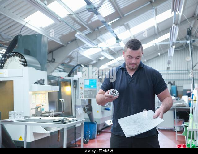 Engineer inspecting machined part in engineering factory - Stock Image