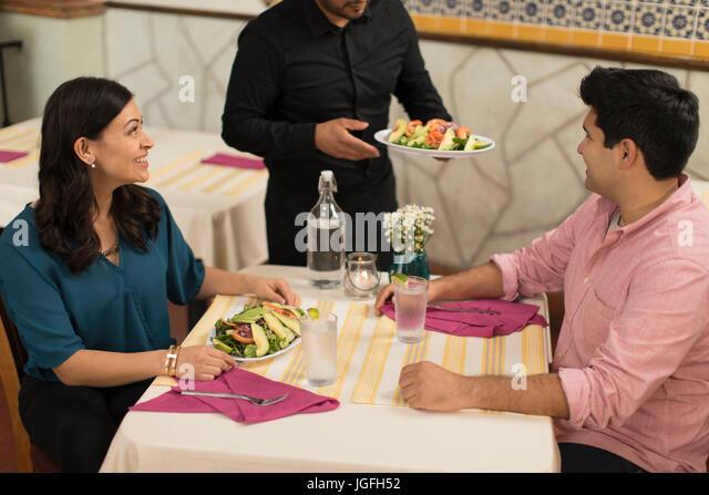 Waiter serving salad to Hispanic couple in restaurant - Stock Image