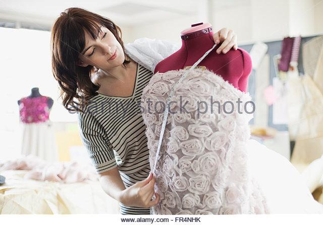 designer measuring dress on dress form - Stock Image