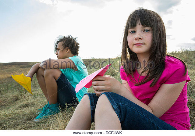 Girls sitting outdoors holding paper airplanes - Stock Image