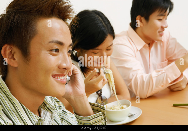 Close-up of a young man talking on a mobile phone with a young couple sitting beside him - Stock-Bilder