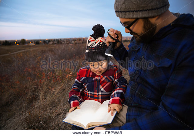 Father and son with book and flashlight outdoors - Stock Image
