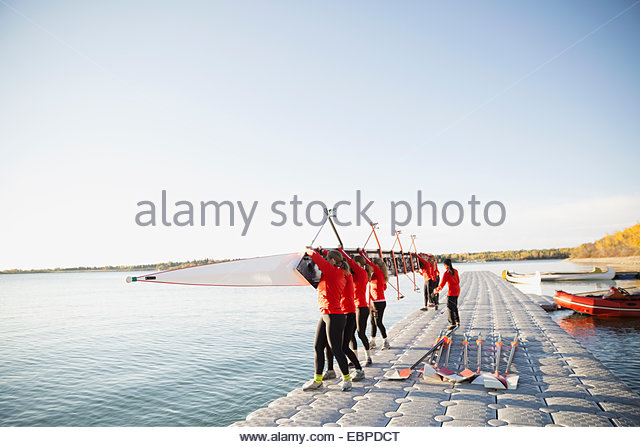 Rowing team holding scull at waterfront - Stock Image