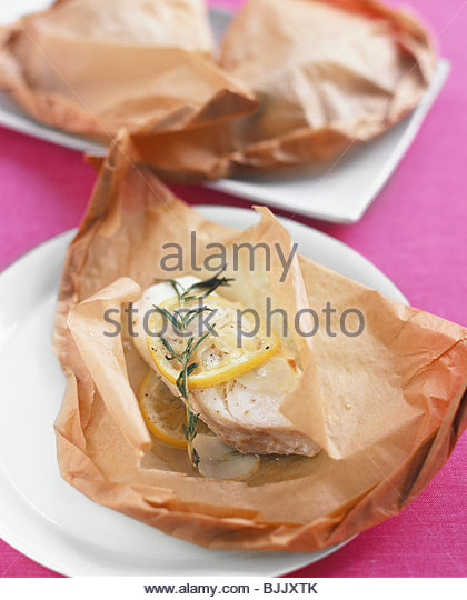 Fish fillet baked in baking parchment with rosemary & lemon - Stock Image