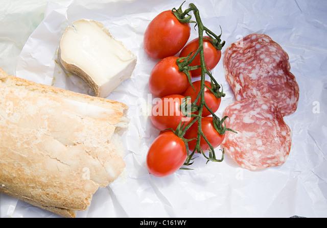 Still life of cheese, ciabatta, plum tomatoes and salami - Stock Image