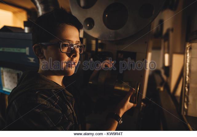 Caucasian tween boy projectionist working in dark movie theater - Stock Image