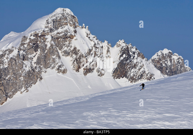 Alpine skier skiing on the Juneau Ice Field and Rhino Peak in the background in Southeast Alaska. Composite - Stock Image
