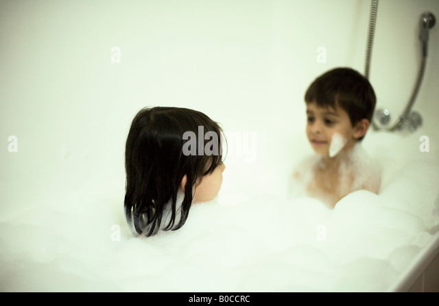 Brother aged six and sister aged four share a bath with lots of bubbles - Stock Image