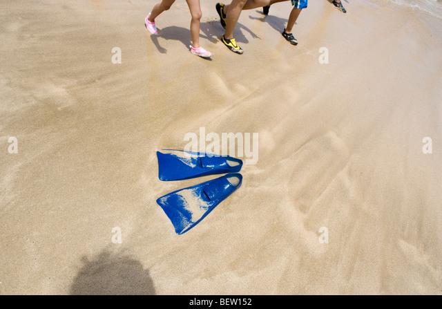 scuba gear flippers left on the beach, kids walking along - Stock Image