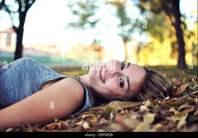 Portrait of smiling young woman lying on autumn leaves - Stock Image