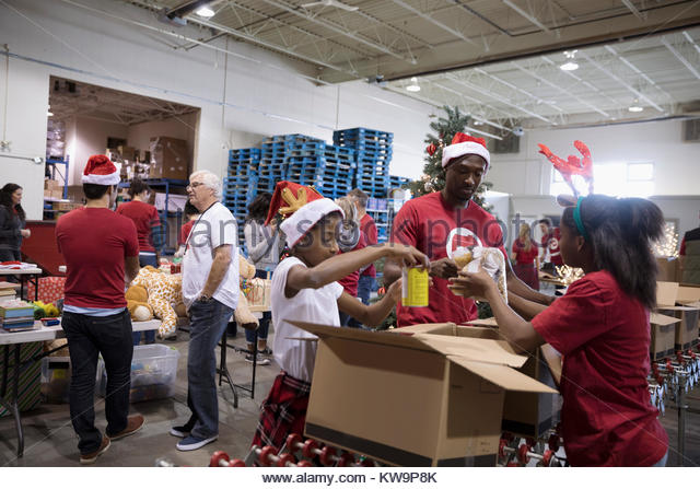 Father and daughters in Santa hats volunteering,filling donation box in warehouse - Stock Image