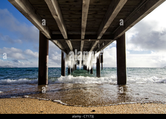 Ice hangs underneath a dock in Lake Tahoe, Nevada. - Stock-Bilder
