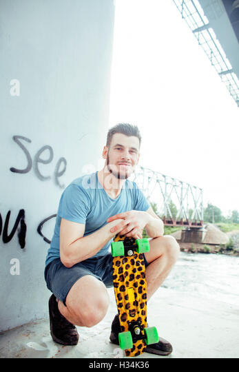 young handsome real hipsrter guy bearded staying under the bridge extreme with leopard skateboard, lifestyle people - Stock Image