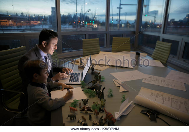 Boy coloring next to dedicated father architect working late at laptop in conference room - Stock Image