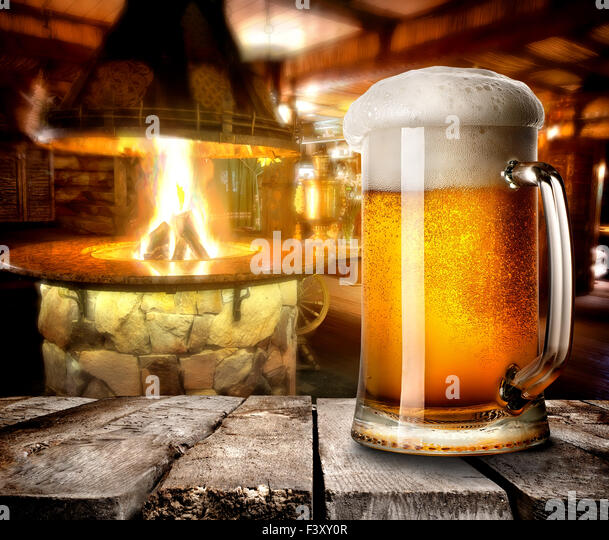 Mug of foamy beer on wooden table in bar - Stock Image