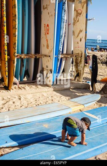 Hawaii Hawaiian Honolulu Waikiki Beach resort Kuhio Beach State Park rental surfboards rent boy toddler - Stock Image