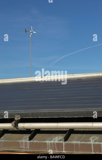 Roof mounted solar heaters and a small wind turbine - Stock Image