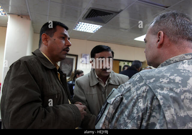 Iraqi doctors explain a case to Maj. Phillipe Perreault, from task Force 1 Medical Group, 28th cash, Level 3 Sather - Stock Image
