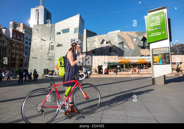 Melbourne Australia Victoria Central Business District CBD Federation Square St. Kilda Road woman teen girl bicycle - Stock Image