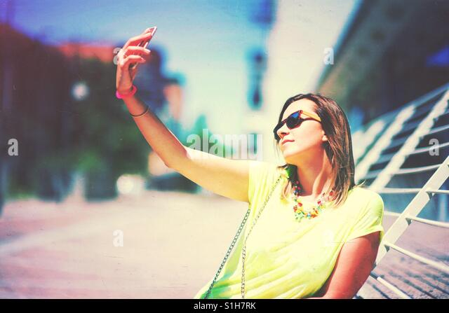 Young woman with sunglasses making a self portrait , selfie - Stock-Bilder