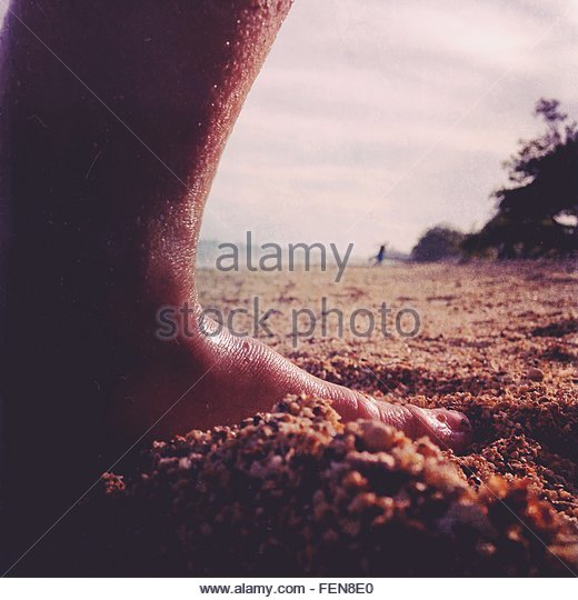 Low Section Of Man Leg On Sandy Beach - Stock Image